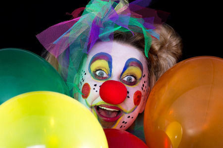 face close up: A colored clown face looks between colorful balloons in to the camera
