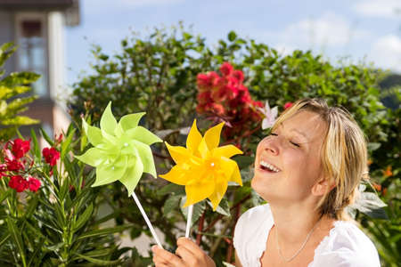 pinwheels: Woman delights in 2 pinwheels and the beautiful weather