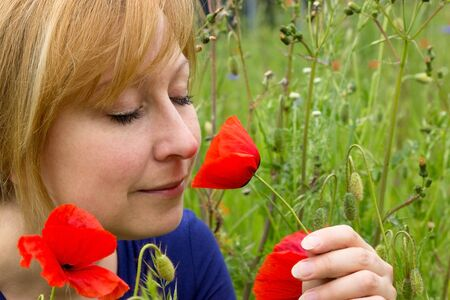 blithe: Woman smells appreciatively at a red poppy flower in a field
