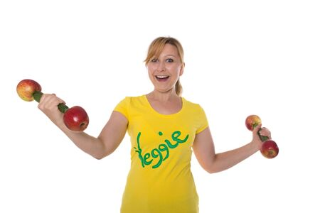 eights: Young attractive woman with weights made of vegetables and fruit is smiling into the camera Stock Photo