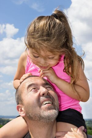 Father takes his daughter on his shoulders for a walk photo
