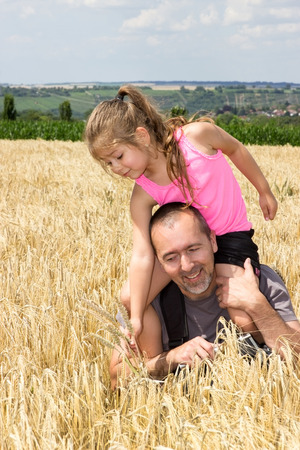 Father and daughter playing in a corn field in the summer photo