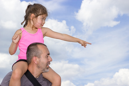 soulfulness: Child sitting on the shoulders of a man pointing in one direction Stock Photo