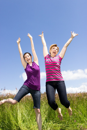 Two girlfriends jumping happily on a green meadow photo