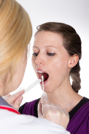 respiratory tract: A young womans throat  is being examined by a doctor