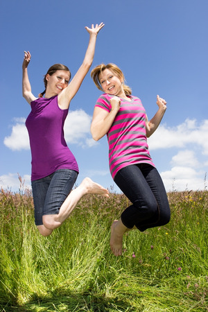 Two young women jumping around on a meadow photo