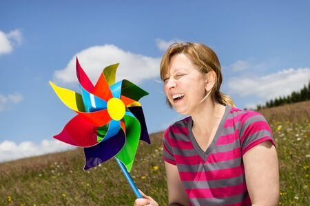 omitted: A young woman with a pin wheel is dazzled by the bright sunshine