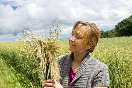 agronomics: A woman standing in a field and holding various types of grain in her hands