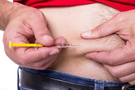 inyeccion: Un hombre se inyecta un medicamento en el vientre