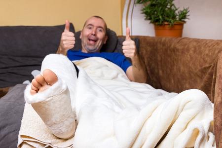 ソファの上に足の骨折で横になっている男