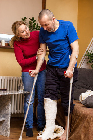 bone health: A man with broken leg taking its first steps with crutches Stock Photo