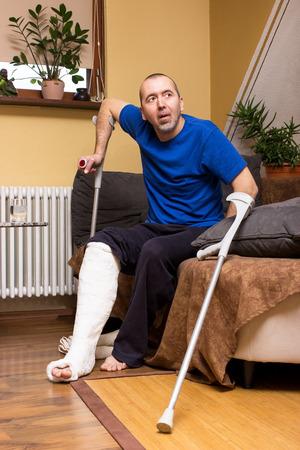 pierna rota: Un hombre con una pierna rota intenta ponerse de pie con muletas de un sofá