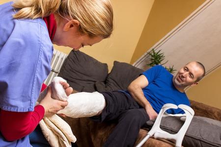 broken leg: A nurse helps a man with a broken leg