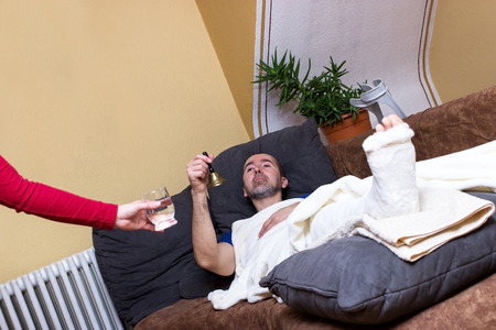 broken leg: A man with a broken leg is lying on a couch and is beeing served