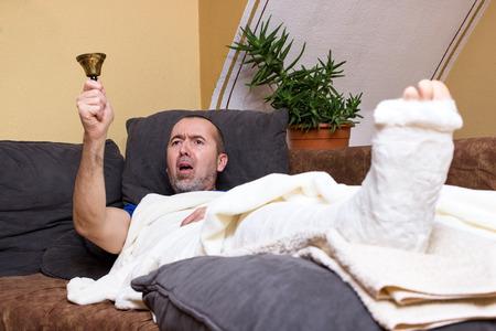 accidente trabajo: Un hombre acostado con una pierna rota en el sofá y sonar furiosamente en busca de ayuda Foto de archivo