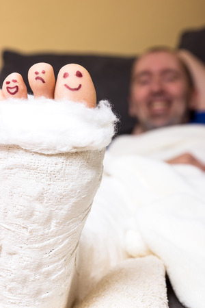 accident patient: Toes looking out the of a plaster painted with funny faces Stock Photo