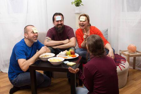 Přátelé sedí spolu a hrát legrační hru s hádáním Reklamní fotografie