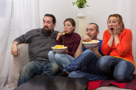 viewers: Two couples sitting together and watching a horror movie Stock Photo