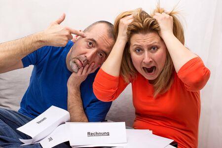 unpaid: A man and a woman in despair because of their unpaid bills Stock Photo