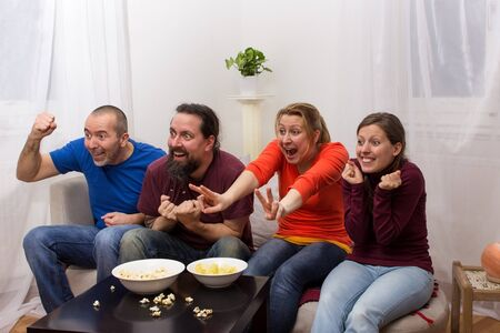 telecast: Four friends sitting in front of a television and cheering