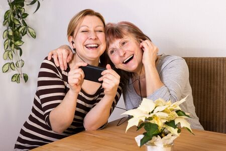 joie: Mother and daughter have fun together while listening to music Stock Photo