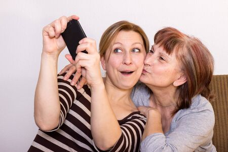 a generation: Mother and daughter having fun taking some selfies Stock Photo