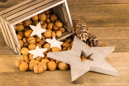 emptied: A fallen box with nuts in front of a wooden background