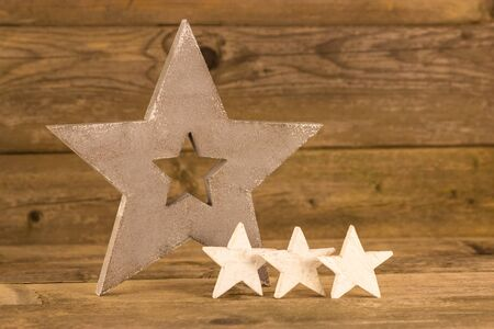 festive pine cones: One big and three small white stars in front of a wooden background