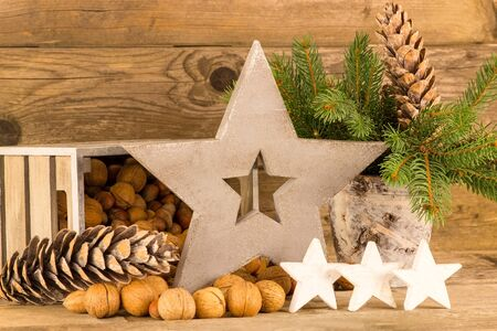 emptied: A decoration of nuts, stars and pine branches in front of a wooden background