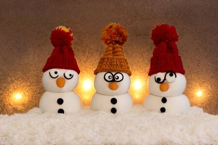 Three snowmen sitting in the snow in front of a  background lightened with candles