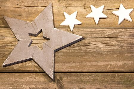 nikolaus: A large and three small stars on a wooden background