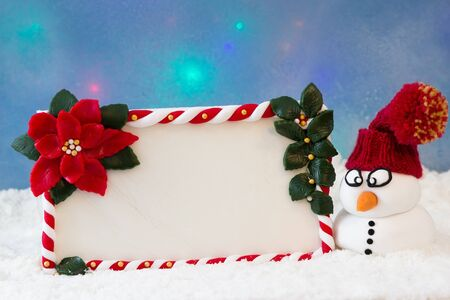christmas paste: A snowman with knit hat beside a greeting card in the snow Stock Photo