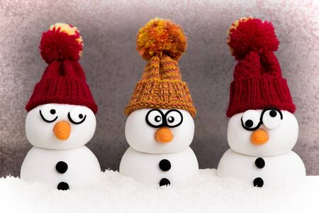 wintery: Three snowmen in front of a gray background
