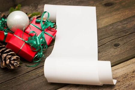 christmas time: A list of Christmas wishes next to several small gifts Stock Photo