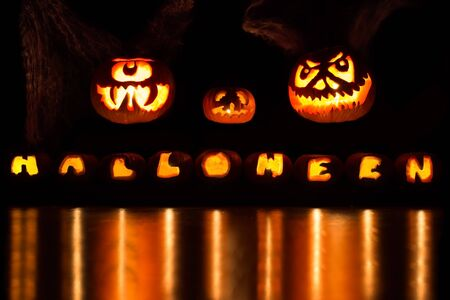 Three large carved pumpkins over a Halloween font