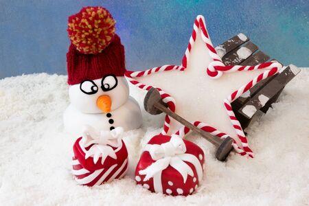 Sněhulák vedle saních s hvězdou a dárky