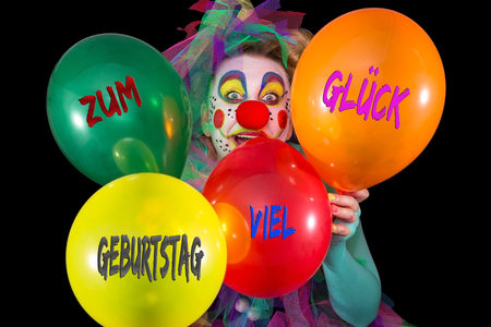 maquillage: A clown holding colorful balloons in his hands in front of a black background Stock Photo