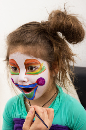 childrens birthday party: A girl is painted by someone as a clown
