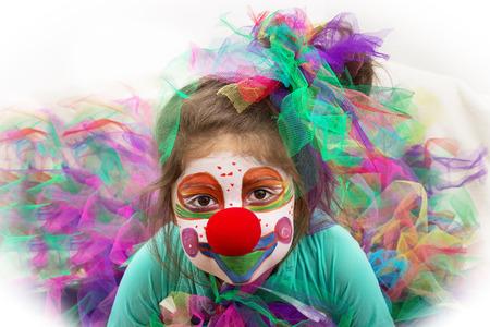 Een klein meisje dieguised opgemaakt als een clown te kijken naar de camera