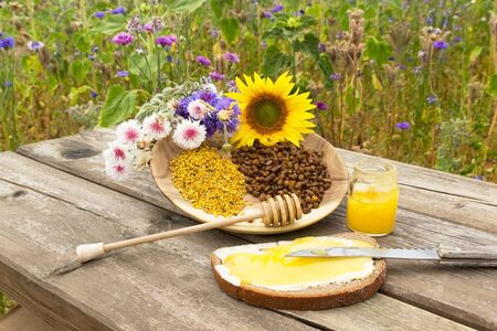 apiculture: A sandwich with honey in front of a wooden plate with apiculture products and flowers Stock Photo