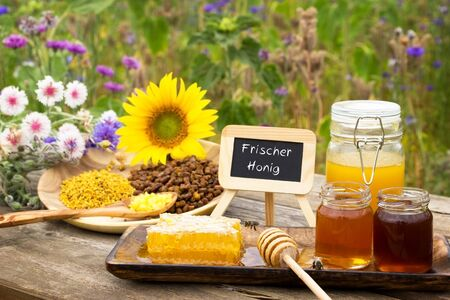 Various bee products on a wooden table with a slate with frischer Honig fresh honey in German Reklamní fotografie