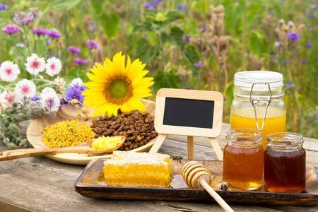 Různé včelí produkty na dřevěný stůl s břidlice