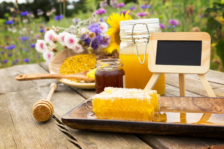 apiculture: A chalkboard surrounded by many apiculture products on a wooden table Stock Photo