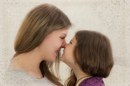 rubbing noses: Mother and daughter rubbing their noses against each other Stock Photo