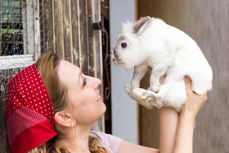 campesinas: Una campesina sosteniendo un conejo blanco en el aire
