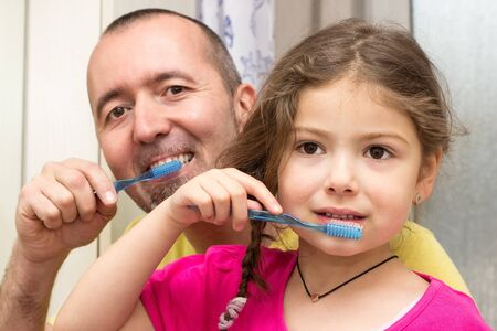 Father and daughter brushing teeth togehther in the bathroom Stock Photo