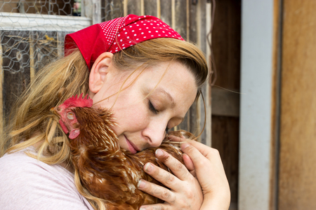 cuddles: A peasant woman cuddles tender with a chicken in her arms
