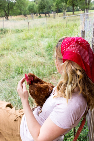 proliferation: A woman with a chicken on her lap looks longingly into the distance Stock Photo