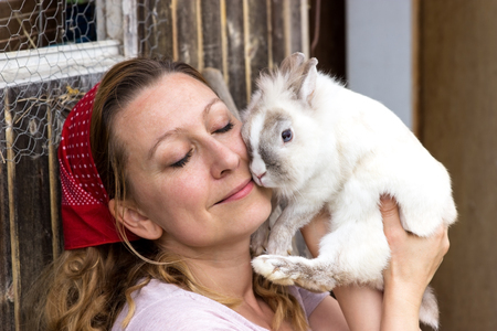animal welfare: Attractive peasant woman cuddles with a white rabbit