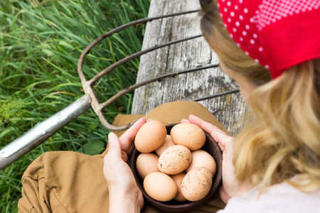 A peasant woman sitting on a bench with a bowl of eggs Stock Photo